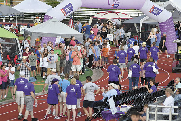 People participate in the Survivor's Lap at the American Cancer Society's Relay for Life in White Bear Lake