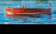 Pat and Susan Oven sit in their Chris-Craft on White Bear Lake watching A scow races.