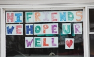 Hopeful covid sign hanging in window