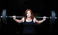 A woman holds a barbell in a photo shoot for BearFitness about empowering women.