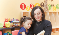 Leah Retamozo reads to a child at Bilingual Child Care & Education Center.