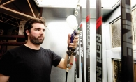 Charlie Igo applies a layer of clear coat to a fresh batch of lacrosse sticks.