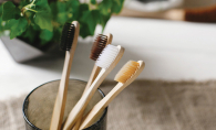 Four bamboo toothbrushes sit in a toothbrush holder.