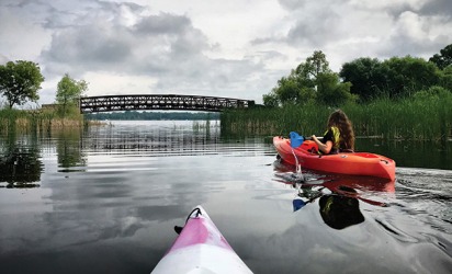 Two people paddle kayaks on White Bear Lake near the Manitou Island bridge.