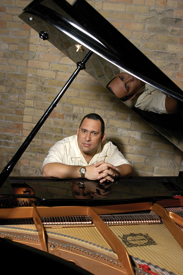 Pianist Nachito Herrera sits at a piano