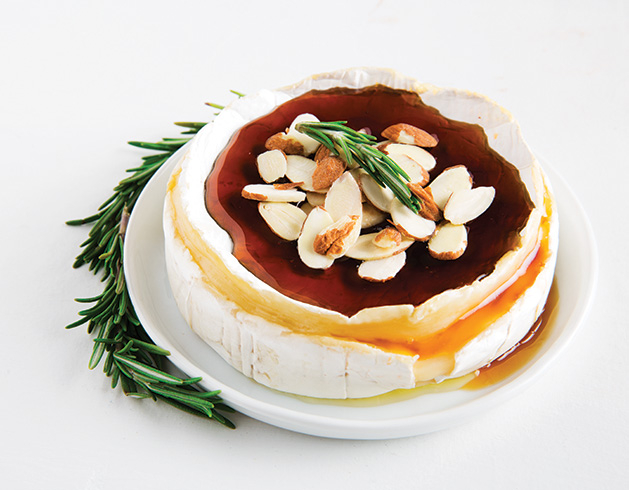 A wheel of brie cheese covered in honey and almonds.