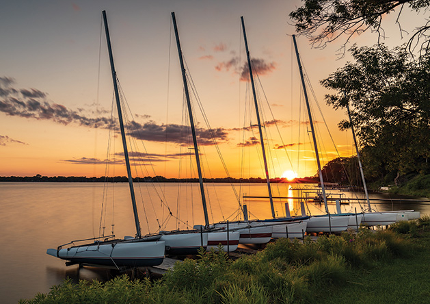 A row of catamarans float on White Bear Lake as the sun sets in the background.