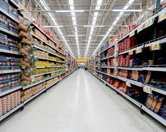 The aisles of a grocery store, shelves stocked with food