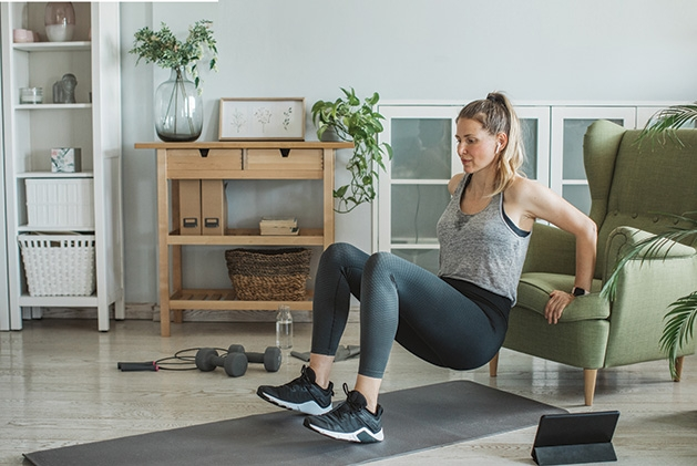 A woman performs online exercises from the YMCA at home.