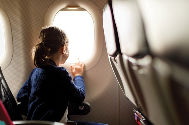 A girl looks out a plane window on a family vacation.