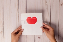 A red heart coming out of a white envelope