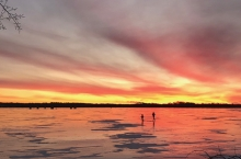 The sun sets as two people walk on the ice on White Bear Lake