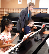 Two children take piano lessons through a partnership with the MacPhail Center for Music.