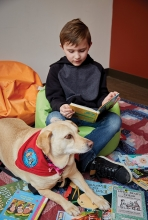 A child reads to a dog during the Paws to Read program