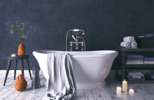 A soaker tub sits in a newly-remodeled bathroom surrounded by candles, towels and other bathroom items.