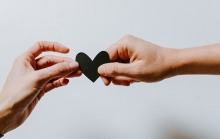 One hand hands another a black paper heart.