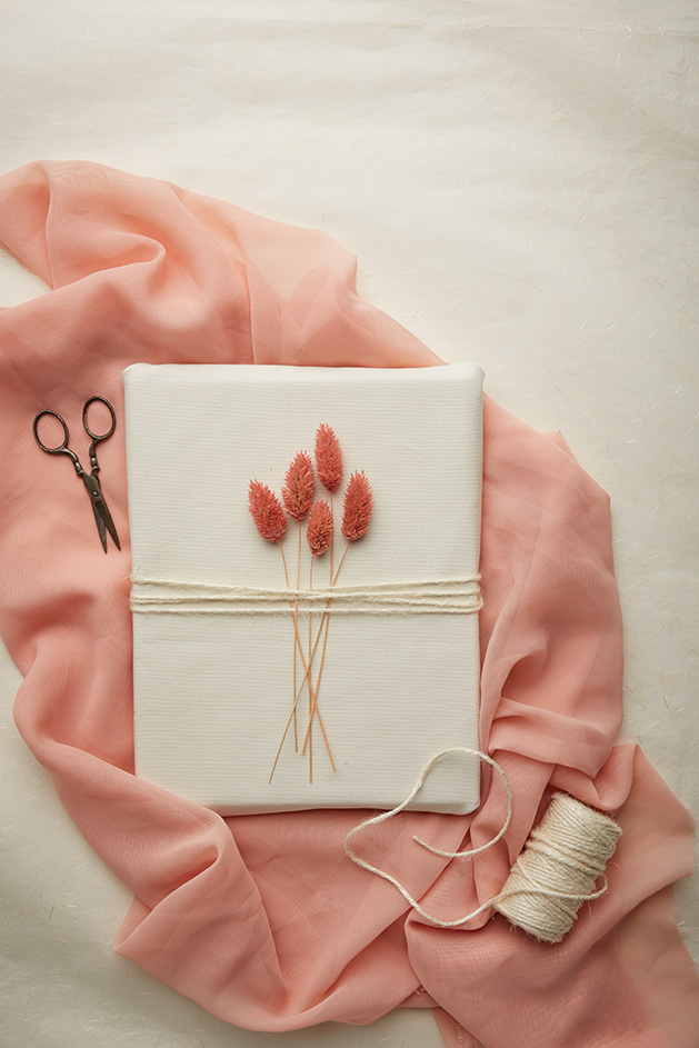 A gift wrapped with twine and pink plants.
