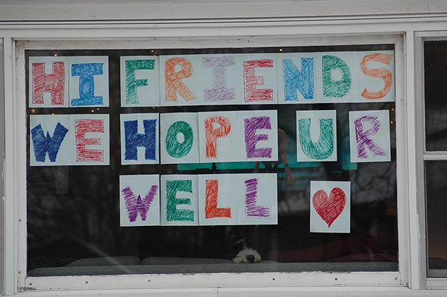 "A dog sits in a window below a sign reading ""Hi Friends We Hope U R Well"""